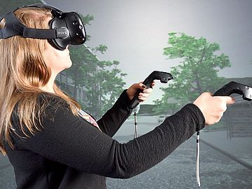 Woman with VR-glasses and controllers in her hand