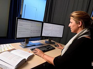 A woman is sitting in front of two PC screens.