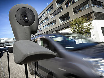 artificial head with microphone on the sidewalk and a car driving by